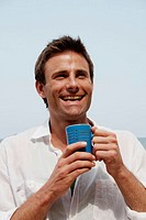 Good-looking man wearing a white shirt and holding a mug of coffee, shot in India