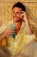 Good-looking man in a yellow shirt drinking a blue cocktail and laughing, shot in India