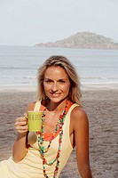 Beautiful blonde woman wearing a yellow vest sat on a beach in India and drinking a cup of coffee