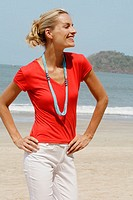 Beautiful blonde woman wearing a red t-shirt and laughing on a beach in India