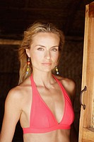 Portrait of a beautiful blonde woman in a red bikini top standing in the doorway of a beach hut in India