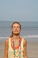 Beautiful blonde woman standing on a beach in India listening to headphones with her eyes closed