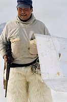 Inuit hunter  Inuit hunter holding a rifle and white blind  He is wearing a garment over his legs made from polar bear fur  Inuit people hunt for ring...
