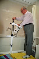 Bathroom for the disabled  Elderly man demonstrates a static floor-fixed hoist, in a bathroom converted for use by a disabled person  The mechanical h...