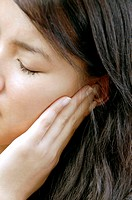 Earache  25 year old Woman holding her hand to her painful ear