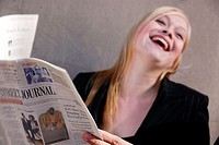 25 yr old caucasian business woman laughing while holding business news paper