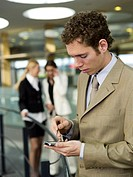 Young businessman using mobile phone, women talking in background