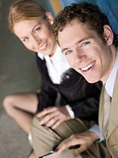 Businesswoman and man sitting smiling, close-up, portrait