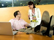 Businessman and woman having lunch break in office, smiling