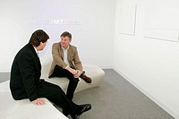 Art Basel, galleries, dealers, Zumtobel, lighting company, men, talk. Convention Center. Miami Beach. Florida. USA.