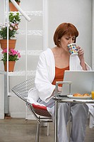 Woman using a laptop at breakfast table