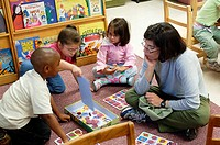 A teacher and students playing a board game in nursery school