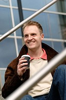 man with coffee, sitting on steps