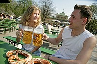 Germany, Bavaria, Munich, English garden, beer garden, pair, cheerfully, steins, Brezen, semi-portrait, gaze-contact,