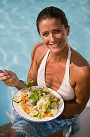 Woman eating a salad near swimming pool, portrait