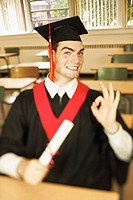 Teenage boy gesturing while wearing cap and gown and holding diploma