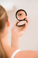 Woman looking in compact mirror
