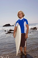 Pre-teen boy with surfboard