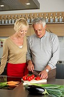 Gray-haired man is cutting tomatoes in a kitchen while standing next to a woman