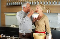 Gray-haired man lets a blond woman taste something he has cooked