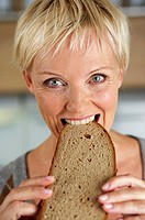 Mature woman with blond hair biting into a slice of bread, close-up