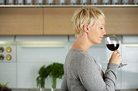 Mature woman with a glass of red wine in her hand, selective focus