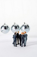 Group of businessmen figurines standing in circle, Newton's cradle in background