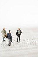 Three businessmen figurines walking over financial newspaper