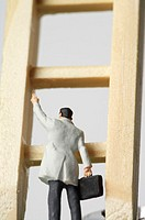 Businessman figurine on a ladder