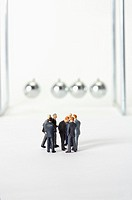 Group of businessmen figurines standing in circle, Newton´s cradle in background