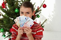 Girl holding banknotes in front of a Christmas tree