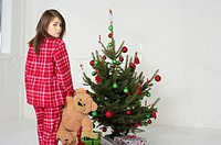 Girl wearing pajamas sneaking off to Christmas tree
