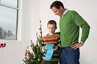 Boy showing list of wishes to father