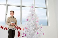 Boy by a white Christmas tree
