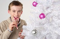 Boy eating a candy cane by a white Christmas tree