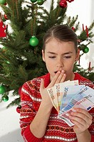 Surprised girl holding banknotes, Christmas tree in background