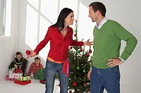 Mother and father arguing in front of Christmas tree, children sitting in the corner