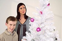 Mother and son next to a white Christmas tree
