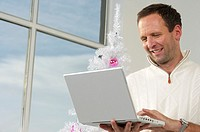 Man using a laptop in front of a white Christmas tree