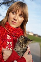 Young woman with a kitten on her arm, close-up (thumbnail)