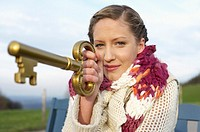 Young woman with scarf and cardigan holding a huge key, close-up