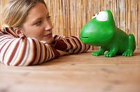 Young woman smiling at an oversized toy frog, selective focus