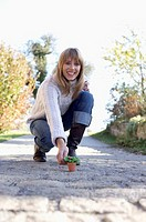 Young woman bending downward to touch a miniature flowerpot, selective focus