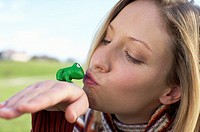 Young woman kissing a toy frog, close-up