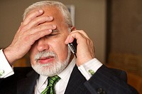 Despaired mature businessman phoning with a mobile phone