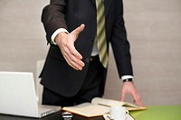 Businessman standing behind his desktop, stretching his hand