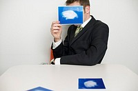 Businessman holding a photo to the camera, clouds