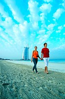 Western tourists walking on the beach near Burj Al Arab hotel in Dubai, UAE