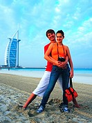 Western couple on the beach near Burj Al Arab hotel in Dubai, UAE