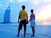 Western couple looking at Burj Al Arab hotel from the beach, Dubai, UAE